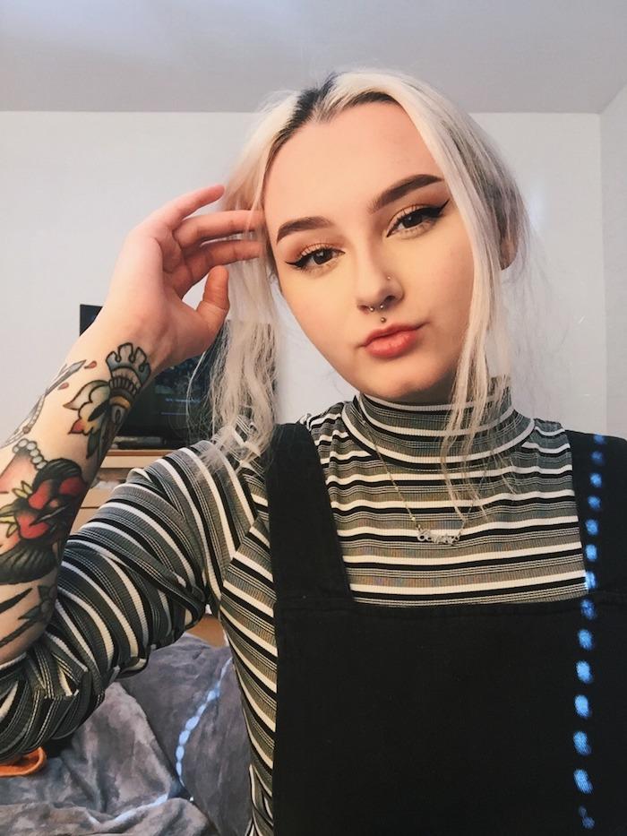 bunte tattoos am arm platinblonde haare lippenpiercing ring Medusа Piercing inspiration schwarzes kleid rollkragenbluse katzenaugen make up