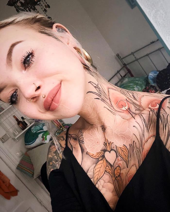 bunte tattoos am körper schwarzes top goldene kreolen geschminktes gesicht schwarze mascara nasenringe mund piercing oberlippe