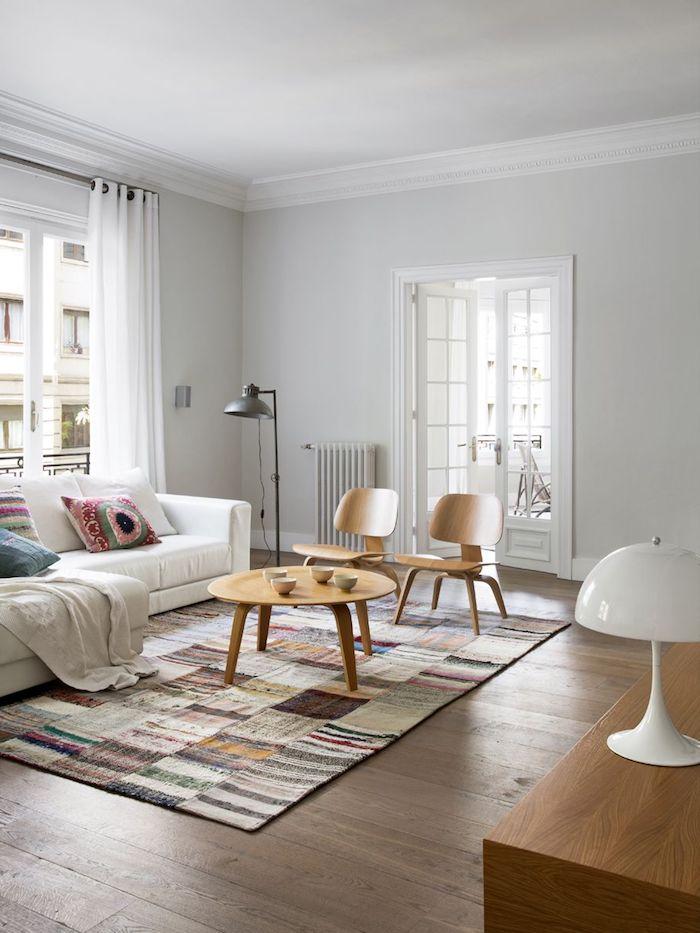 bunter teppich im skandinavischen stil scandi style wohnzimmer einrichten holzstühle und runder holztisch weißer couch große fenster mit weißen gardinen