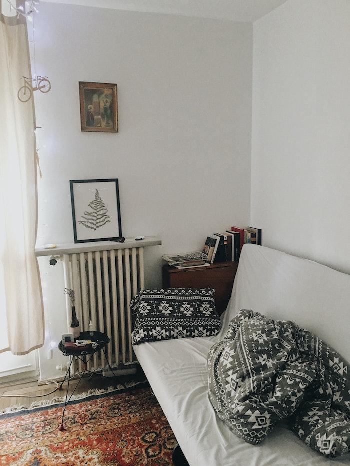 bunter teppich weißer couch mit schwarzen kissen skandinavischer wohnstil kleines wohnzimmer im scandi style einrichten kleiner runder tisch dekoration bilder