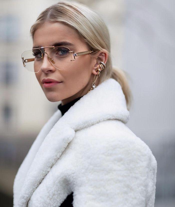 caro daur street style inspiration kurze blonde haare niedriger zopf verschiedene ohrringe brillenmode 2020 damen weißer flauschiger mantel