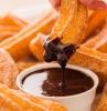 churros con chocolate rezept eine hand und ein teller mit churros puderzucker und schokolade