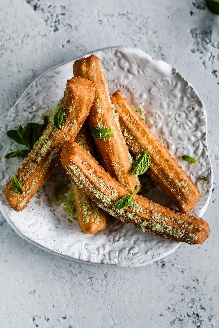 churros rezept ein weißer teller mit churros und mit matcha und grünen blättern aus frischer pfefferminze