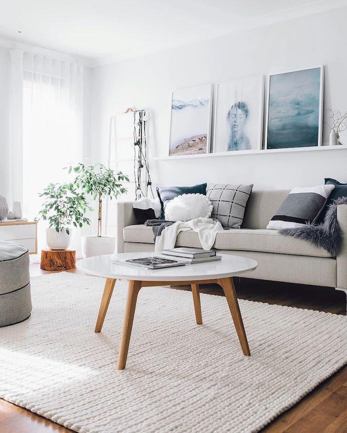 cremefarbener skandinavischer teppicu weißer kaffeetisch mit vier beinen aus holz beiger sofa mit verschiedenen kissen
