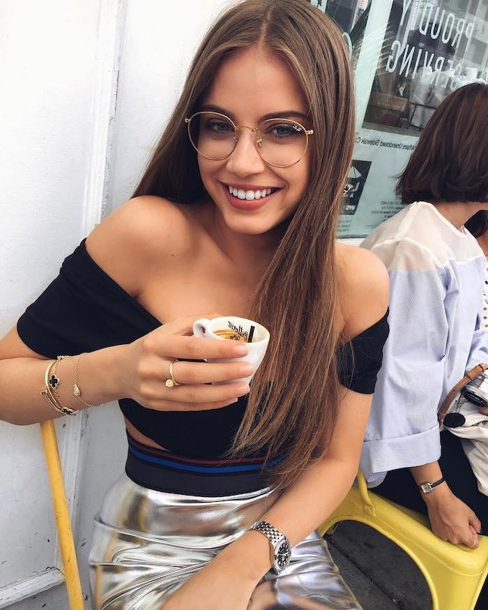 dame mit langen braunen haaren schwarzes top silberner rock brillen trends 2020 damen elegante accessoires ringe armbänder uhr