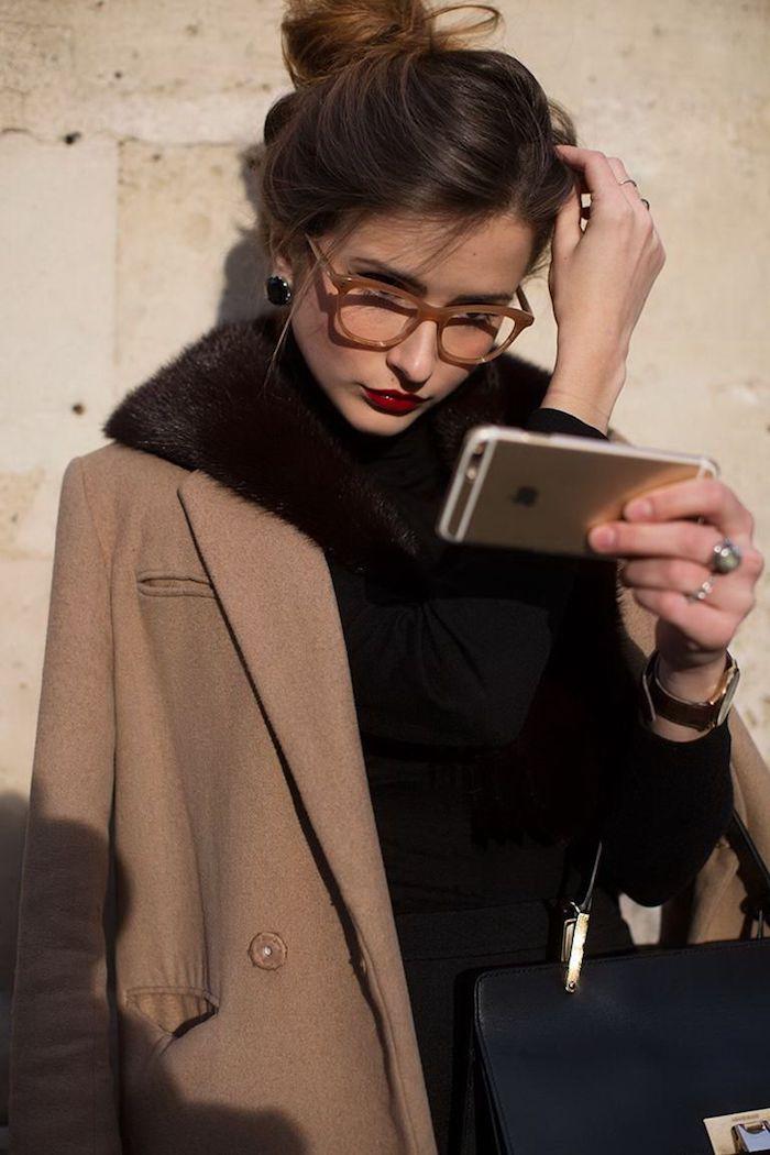 damen brillen trends dickes brillengestell inspiration stylisch angezogene dame brauner mantel schwarze tasche hochgesteckte braune haare