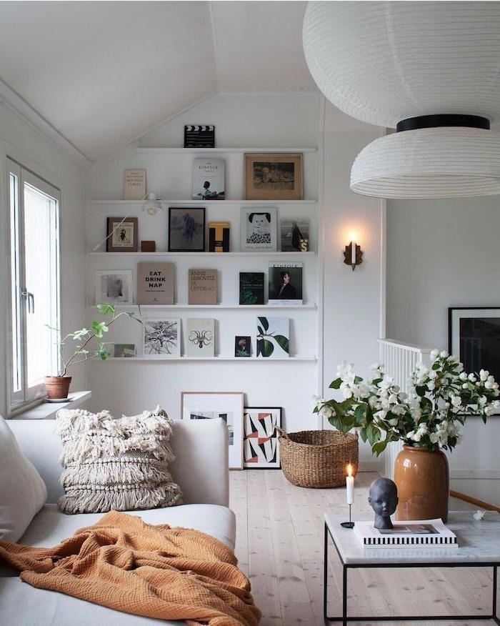 dekoration kleines wohnzimmer scandi style viele deco bilder vase mit weißen blumen kaffeetisch mit schwarzen beinen