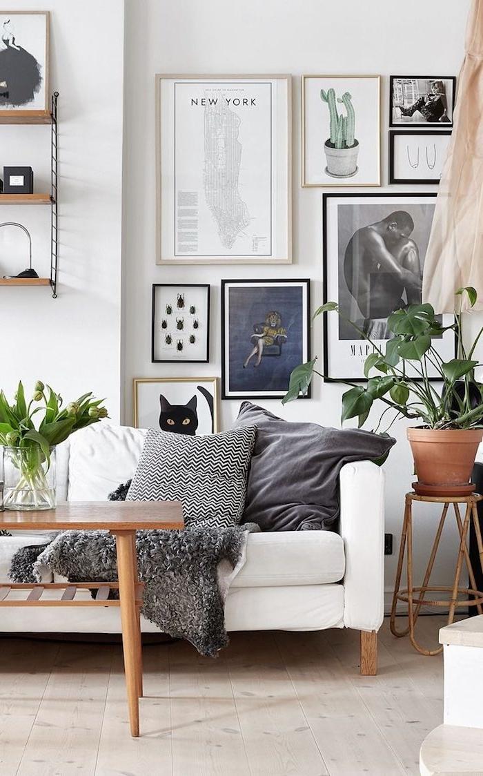 dekoration wohnung mit pflanzen weißer couch graue kissen kaffeetisch aus holz aufgehängte bilder und zeichnungen möbel skandinavisch