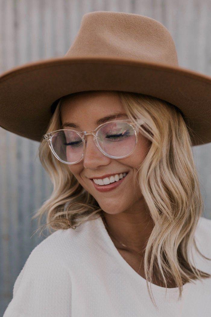 durchsichtige brille trends 2020 damen modernes outfit mittellange blonde haare weiße bluse casual outfit moderner fedora hut in braun