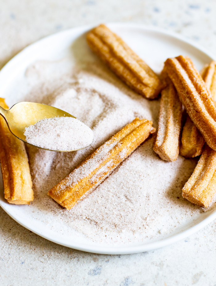 ein churros rezept löffel mit puderzucker ein weißer teller mit churros eine schritt für schritt anleitung