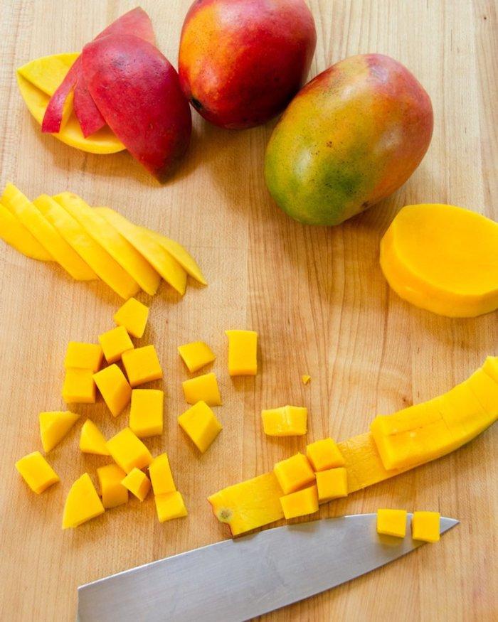 ein holzbrett mit messer und mango in vielen kleinen gelben scheiben grüne und rote mango schale