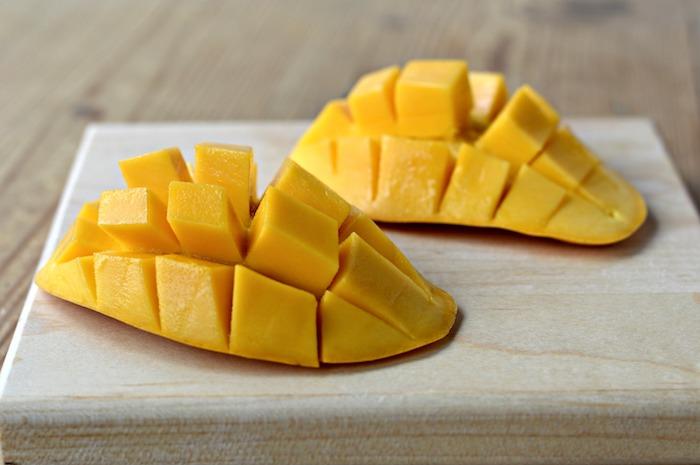 ein holzbrett und zwei große orange mango igel wie kann man eine mango schneiden