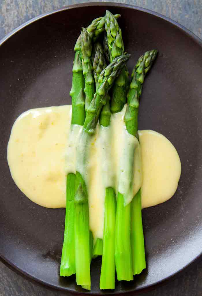 ein köstliches rezept für spargel mit sauce hollandaise ein teller mit langen grünen spargelstangen