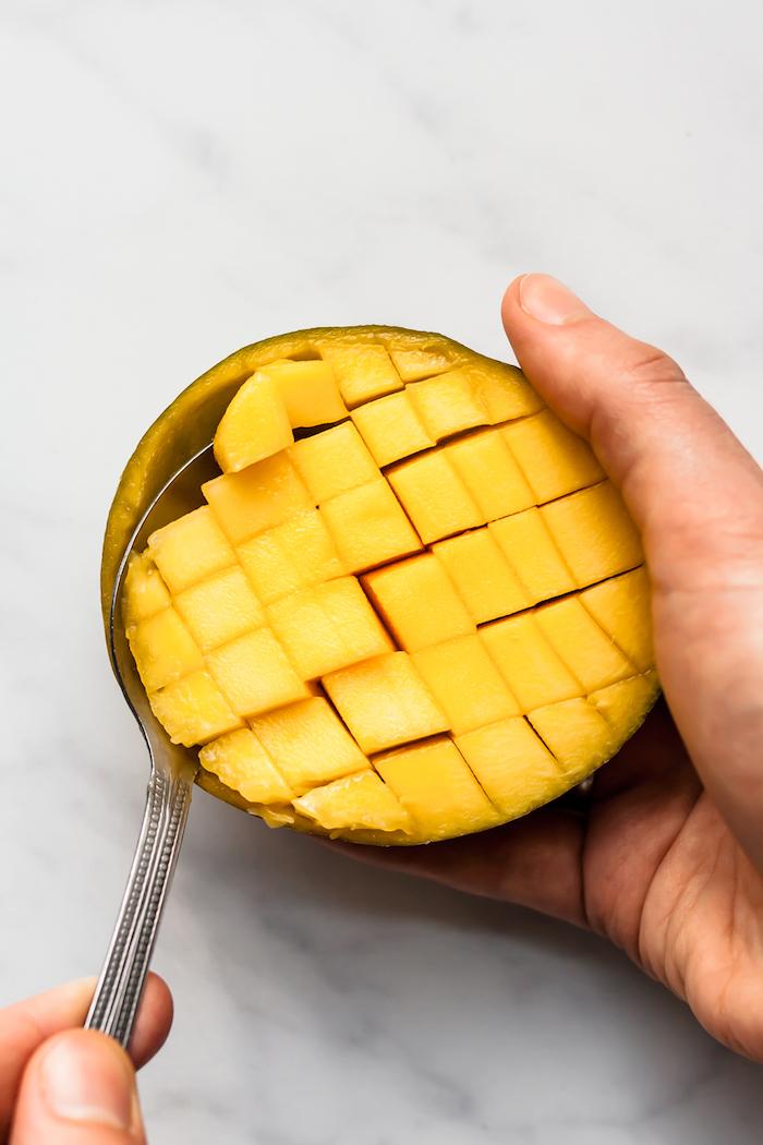ein löffel und eine geschnittene mango wie kann man eine mango schneiden anleitung