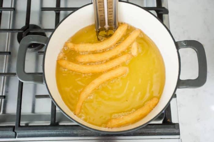 ein topf mit öl und langen spanischen churros frittieren ein churros rezept selber machen