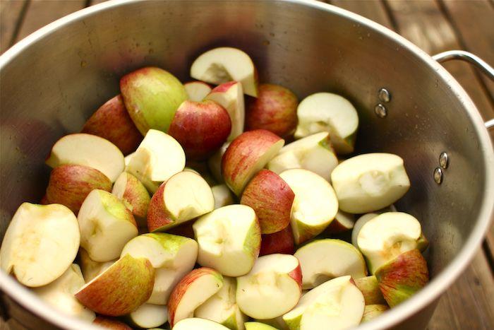 ein topf mit vielen kleinen geschnittenen grünen und roten äpfelwürfeln apfelmus selber machen diy anleitung