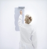 woman painting a wall with a paint roller
