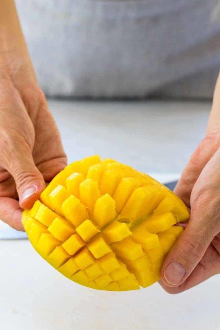 eine frau mit grauem t shirt ein mango igel geschnittene kleine scheibe mango wie erkenne ich eine reife mango