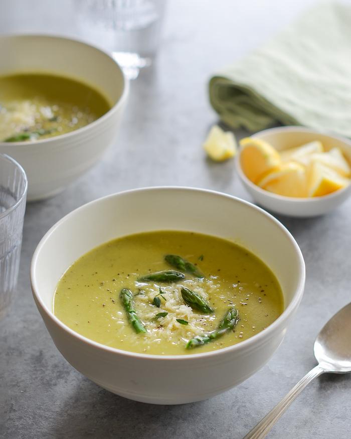 eine grüne suppe mit blättern aus basilikum eine weiße schüssel suppe mit pfeffer und langen spargeln