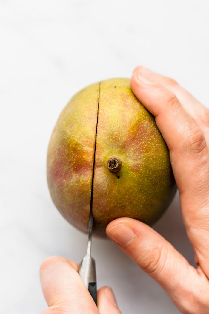 eine hand mit messer schritt wie kann man eine mango schneiden eine reife mango
