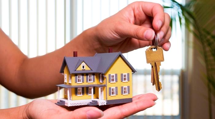 eine hand und schlüssel tipps zum schnellen immobilienverkauf ein gelbes haus