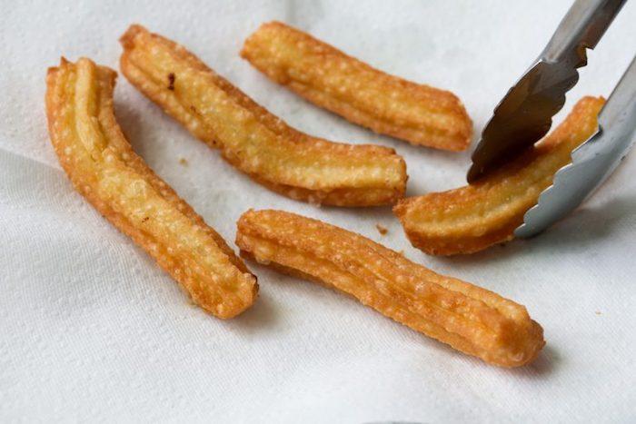 eine schritt für schritt anleitung für spanische churros löffel und churros mit puderzucker