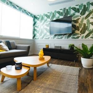 einrichtungstrends 2020 florale tapeten tropische muster möbel trends 2020 grauer couch gelbe kissenn holzboden