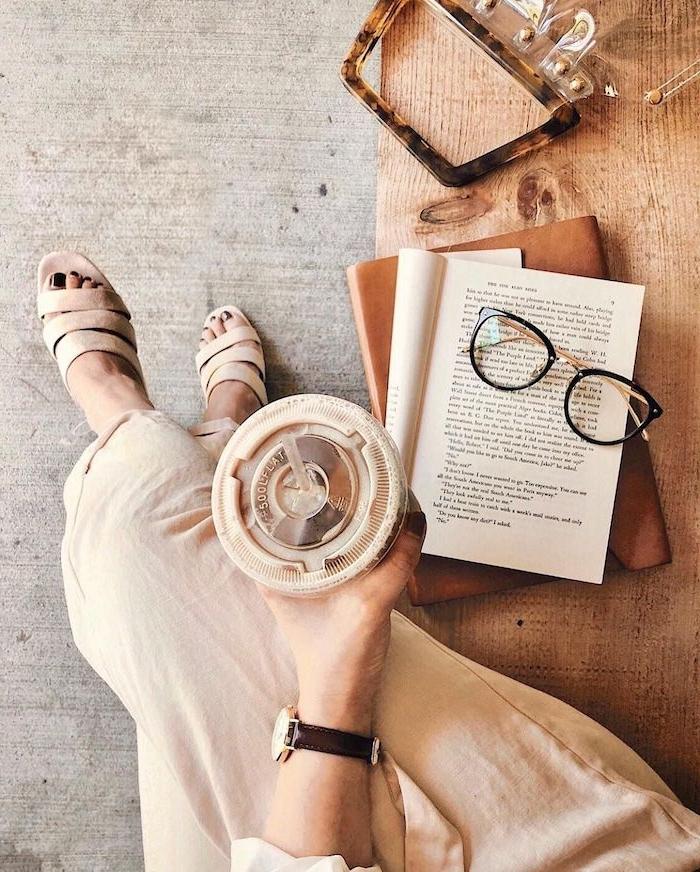 elegantes monochromes outfit beiger rock und sandalen schwarzer nagellack aufgeschlagenes buch damen brillen schwarzes brillengestell