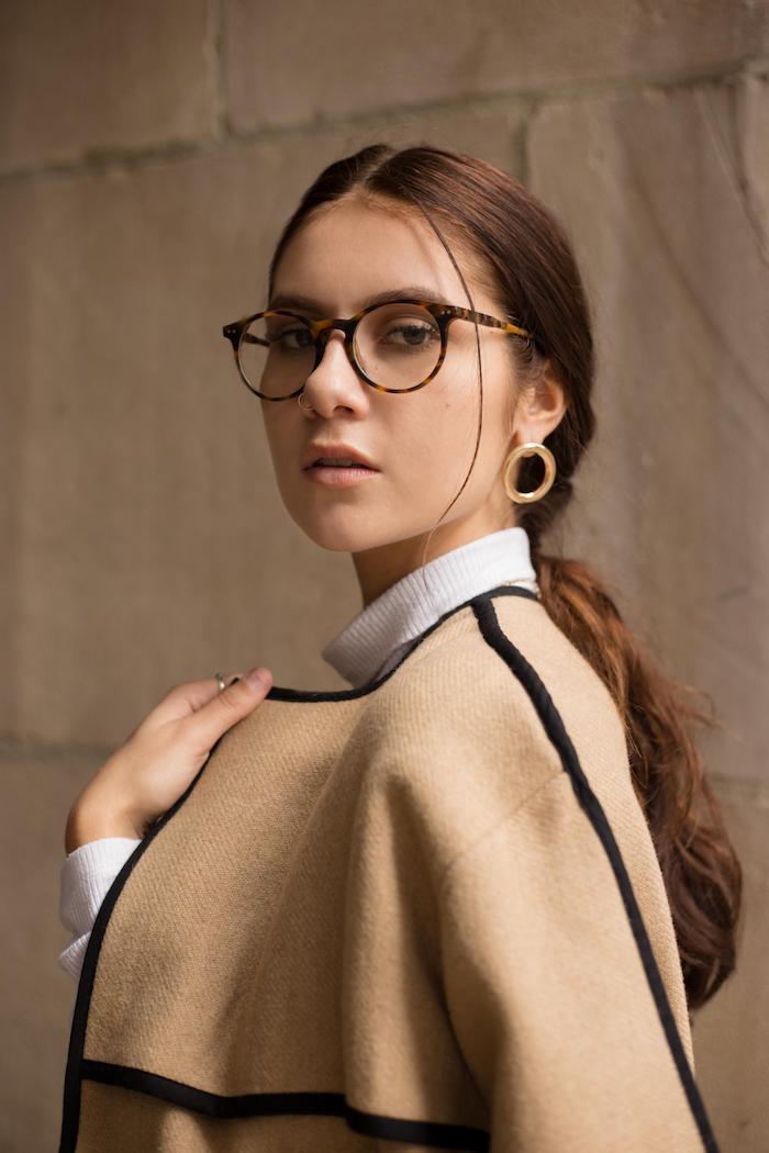 elegantes styling brauner poncho mit weißer bluse braun rote haare im niedrigen zopf runde ohrringe modische brillen trends 2020 damen schwarz braunes brillengestell