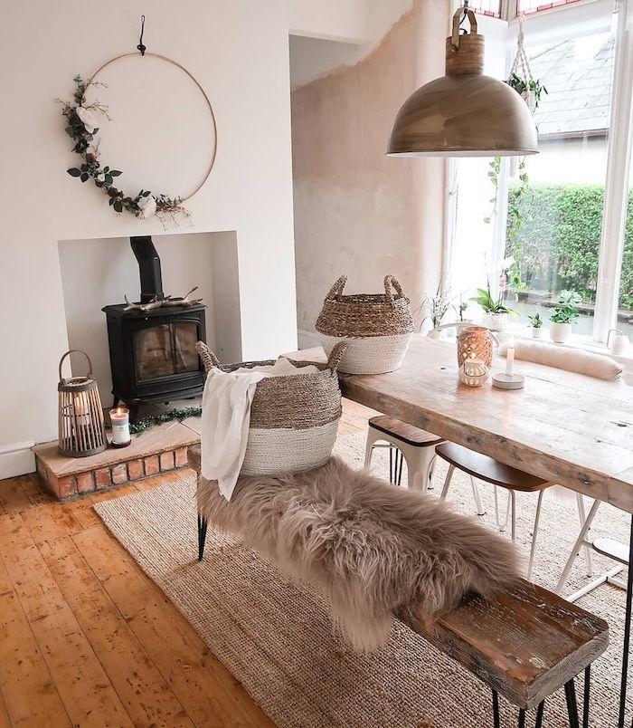 esstisch skandinavisch wohnzimmer mit essbereich und kamin holztisch mit holzbank großer kranz mit blumen beiger scandi teppich flauschige decke