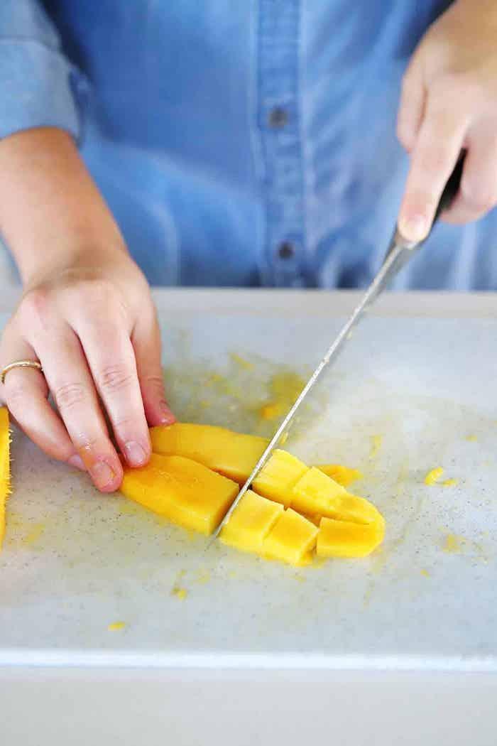 frau mit blauem hemd ein messer und gelbe geschnittene scheiben aus mango
