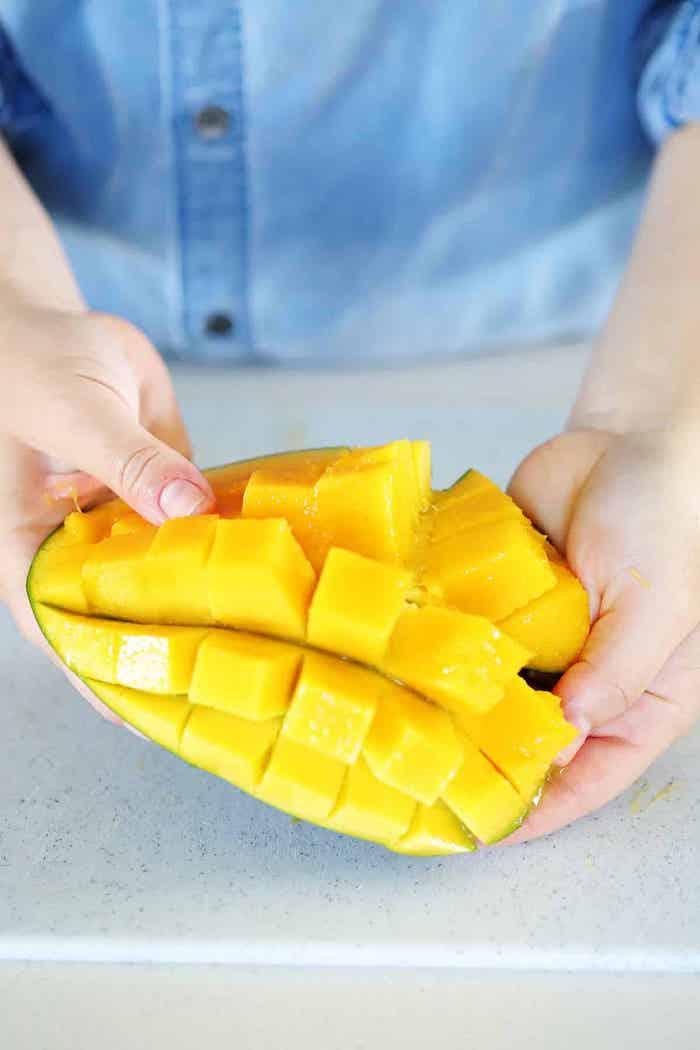 frau mit blauem hemd wie kann man eine mango schneiden einen mango igel selber machen
