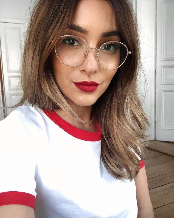 frau mit braunen haaren mit blonden strähnen rot weißes t shirt moderne brillen damen trends 2020 runde brillengestelle dezentes make up roter lippenstift