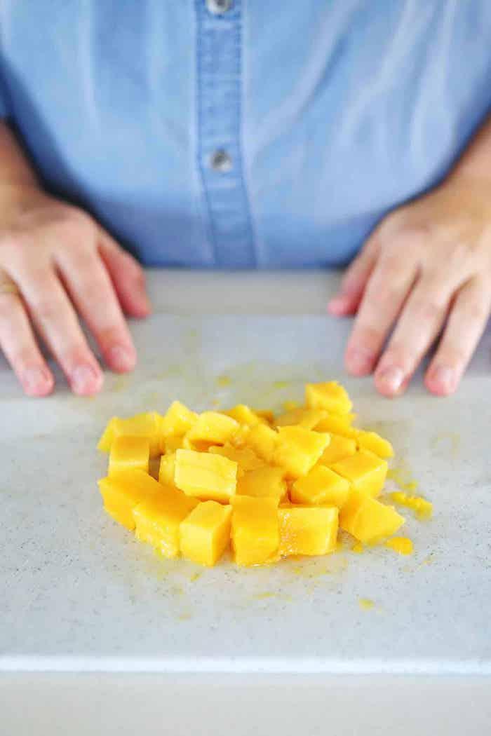 frau mit einem blauen hemd geschnittene mangos wie kann man eine mango schneiden
