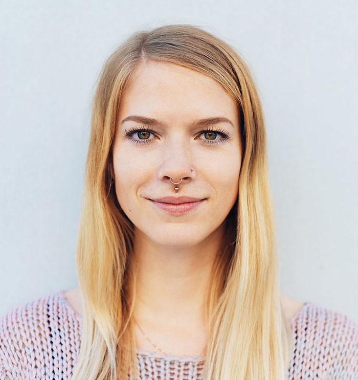 frau-mit-langen-blonden-haaren-rosa-pullover-oberlippenpiercing-medusa-piercing-goldener-nasenring-minimales-make-up