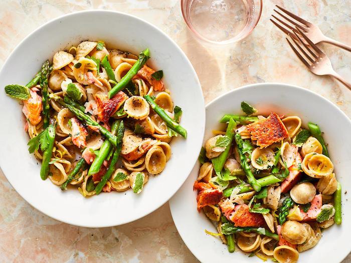 gabel und ein glas zwei weiße teller mit pasta mit spargelstangen und basilikum und pfeffer und tomaten
