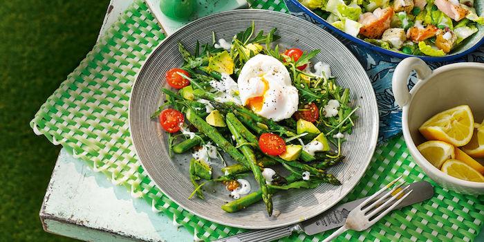 gabel und meser eine kleine weiße schüssel mit zitronen spargel rezepte salat mit grünen spargeln tomaten und eiern