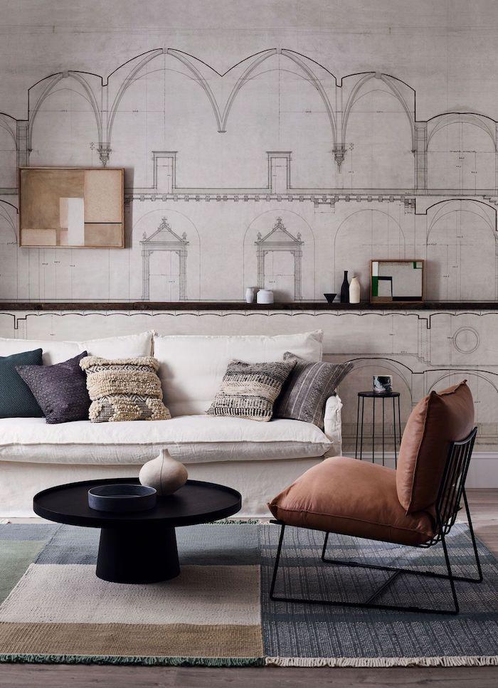 gedämpfte farbpalette wohnzimmer braun roter stuhl weißer couch bunte kissen schwarzer runder kaffeetisch zeichnugn an der wand