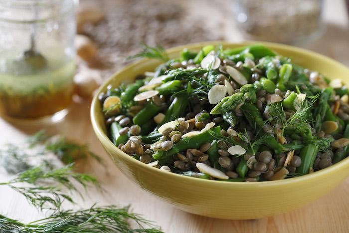 gelbe schüssel mit bohnen basilikum und langen grünen spargelstangen ein tisch aus holz spargel rezepte
