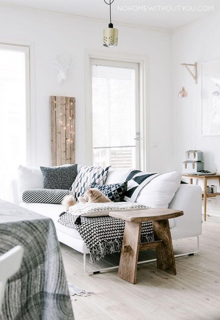 gemütliche und schicke inneneinrichtung in weißen farben mit holzmotiven weißer couch mit dunklen kissen skandinavisches design interior