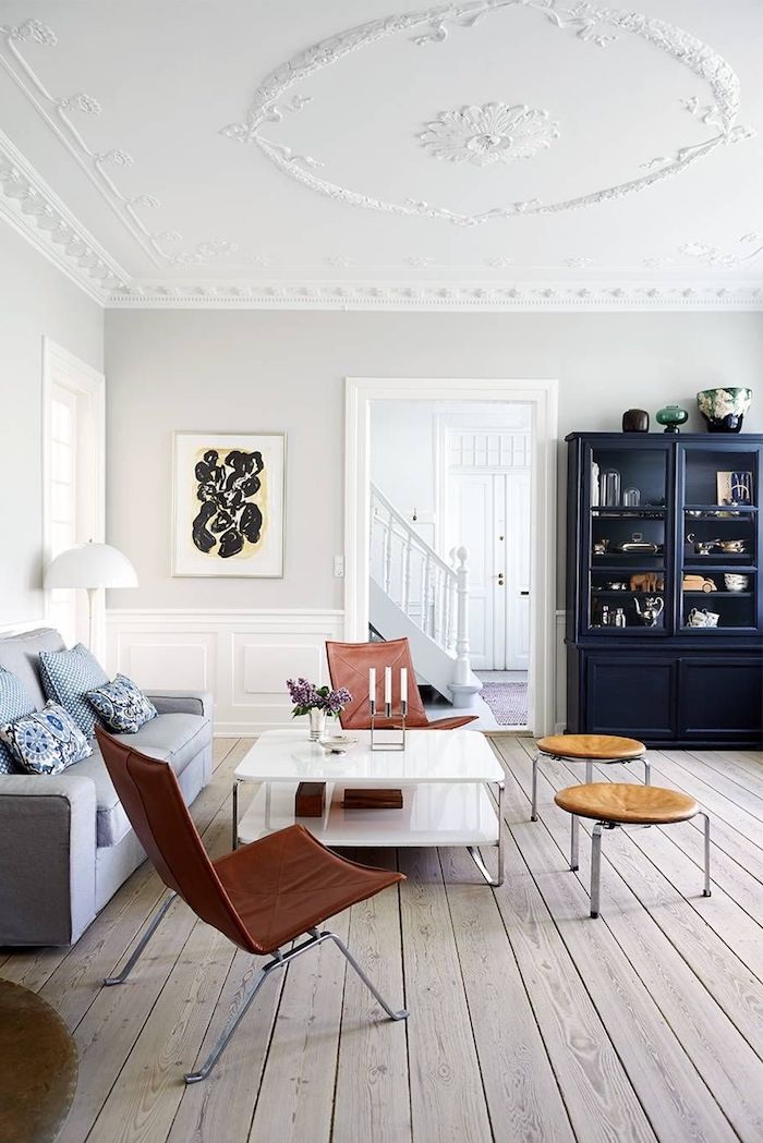großer schrank in dunkelblau braun rot farbene stühle grau blauer couch weiße wände holzboden schwedische möbel wohnzimmer im skandinavischen stil einrichten