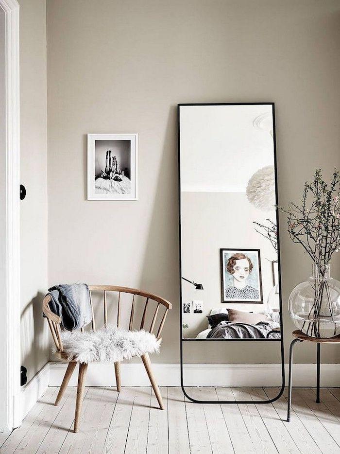 großer spiegel mit schwarzem rahmen wandfarbe neutrale farben skandinavisches wohnzimmer runde vase mit zweigen holzstuhl interior design inspiration ideen