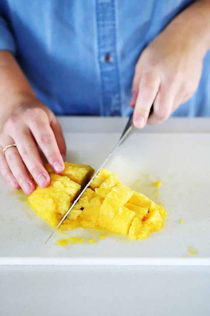 hand mit ring und messer und mango in scheiben eine diy anleitung eine mango schneiden