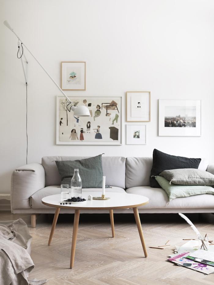 interior design in netralen farben grün grau holz skandinavisches design scandi style wohnzimmer moderne bilder an die wand couchtisch mit vier beinen