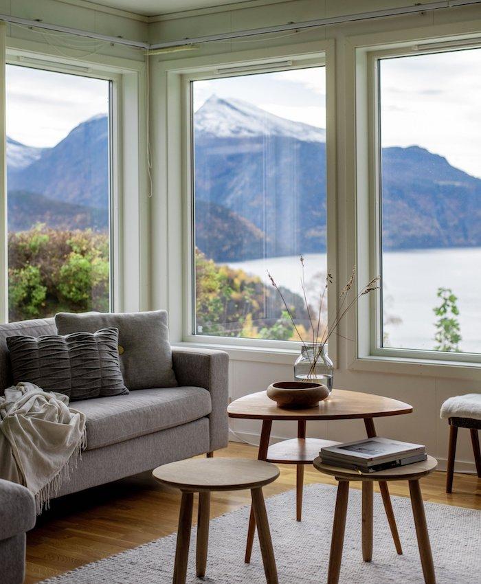 kleine und große tische aus holz graues sofa mit kissen skandinavisches wohnzimmer einrichten große fenster mit aussicht zum see und bergen
