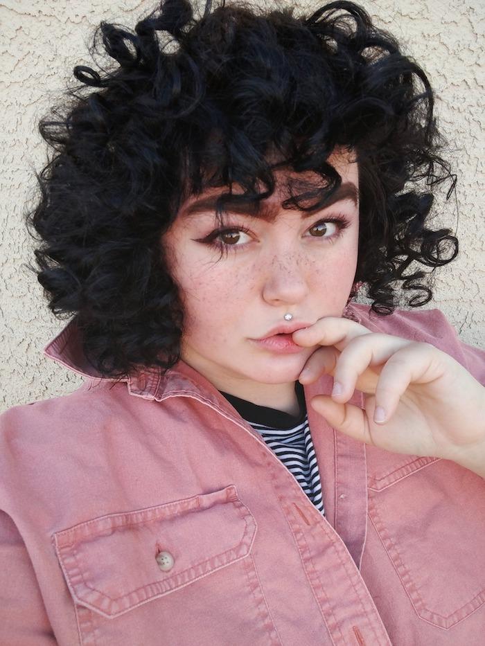 kurzhaarfrisuren für lockiges haar katzenaugen make up pinkes hemd schwarz weißes t shirt mund piercing medusa ideen und inspiration