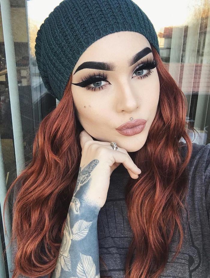 lange gewellte rote haare graue mütze und t shirt tattoos am arm volle augenbrauen katzenaugen make up glitzernder lippenstift lippeniercing mitte