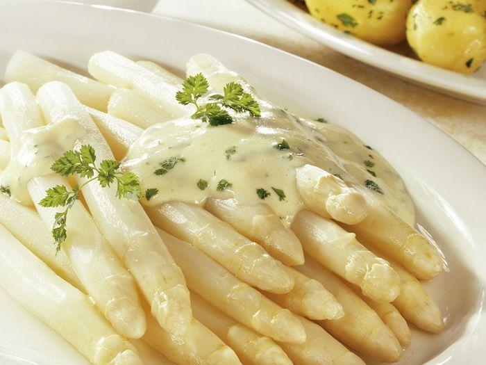 lange weiße gekochte und geschälte spargelstangen mit soße hollandaise und mit blätter aus frischer petersilie
