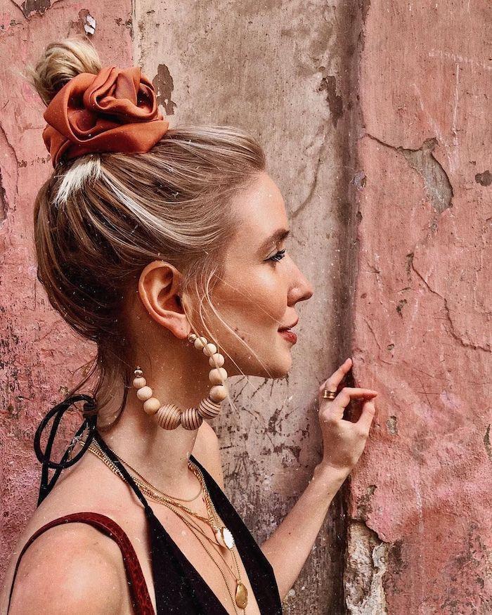 leonie hanne inspiration boho chic style blonde haare hochsteckfrisur dutt mit scrunchy große runde ohrringe mit holzkugeln schlichte halsketten schwarzes top