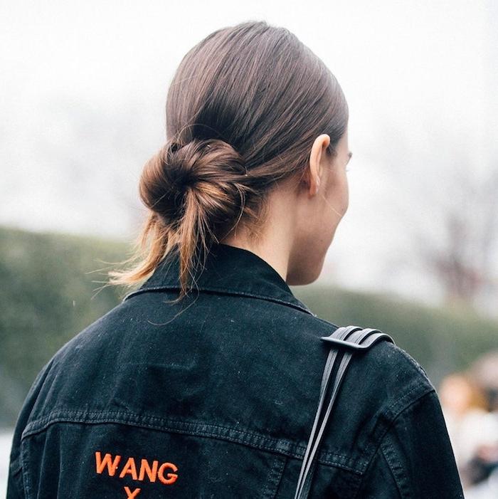 lockerer dutt niedriger haarknoten frisuren für lange haare street.style ideen schwarze jeansjacke und tasche braune haare dutt frisuren selber machen